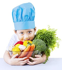 A young boy wearing a chef hat and holding on to a big bowl of vegetables
